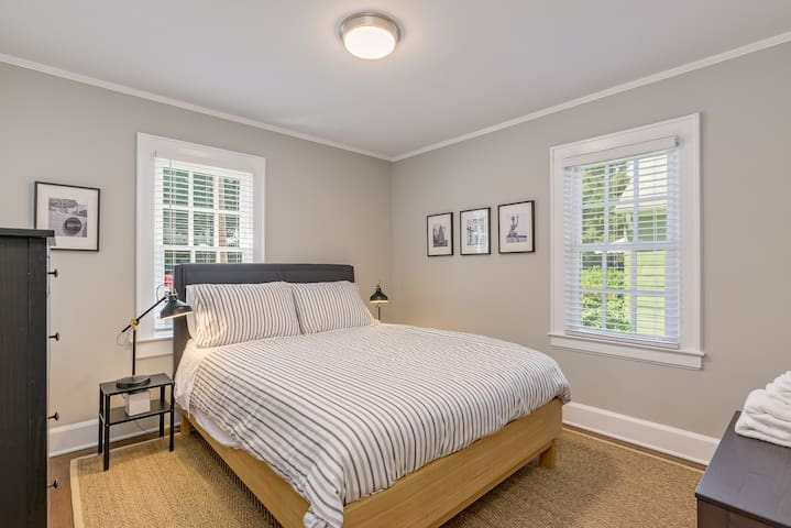 Second bedroom with comfortable queen bed. Bedroom includes dresser, full length mirror, closet, and bench seat