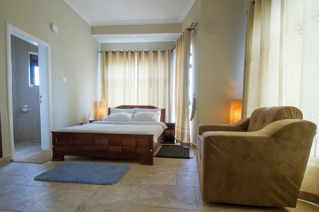 Upstairs Master Bedroom has a King-size bed, trendy bedside/desk lamps, fresh clean sheets, own modern bathroom with running hot water, and a Juliet balcony overlooking the glorious views of Kampala hills.