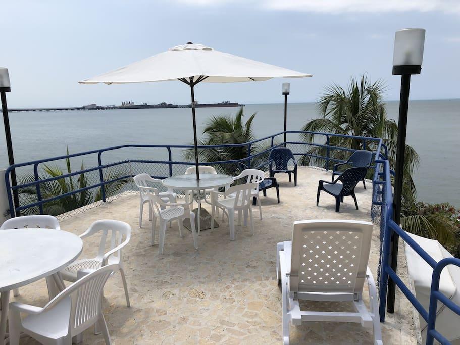 Terraza Principal con asoleadoras, sillas y parasol.