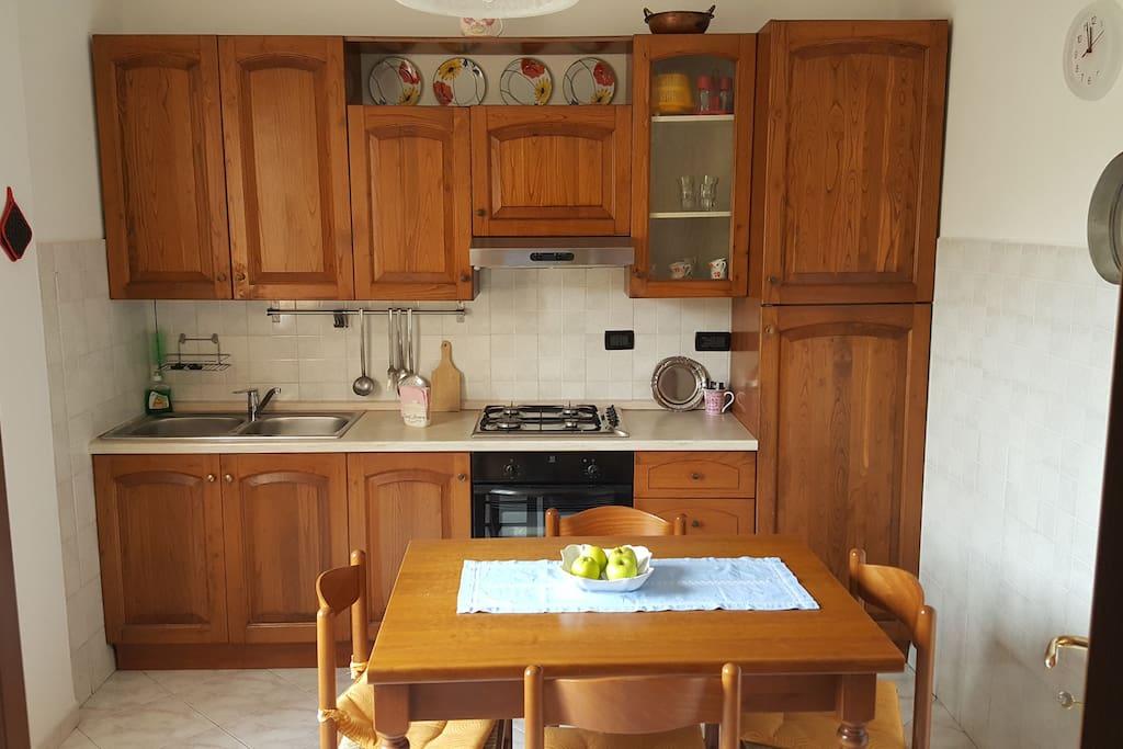 cucina dotata di frigo, frezeer, forno, bollitore elettrico, stoviglie, pentole, biancheria da cucina.