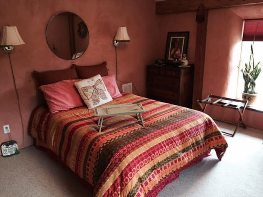 Large room with great countryside views, closet, dresser, and dressing table. All draped in warm adobe colors.