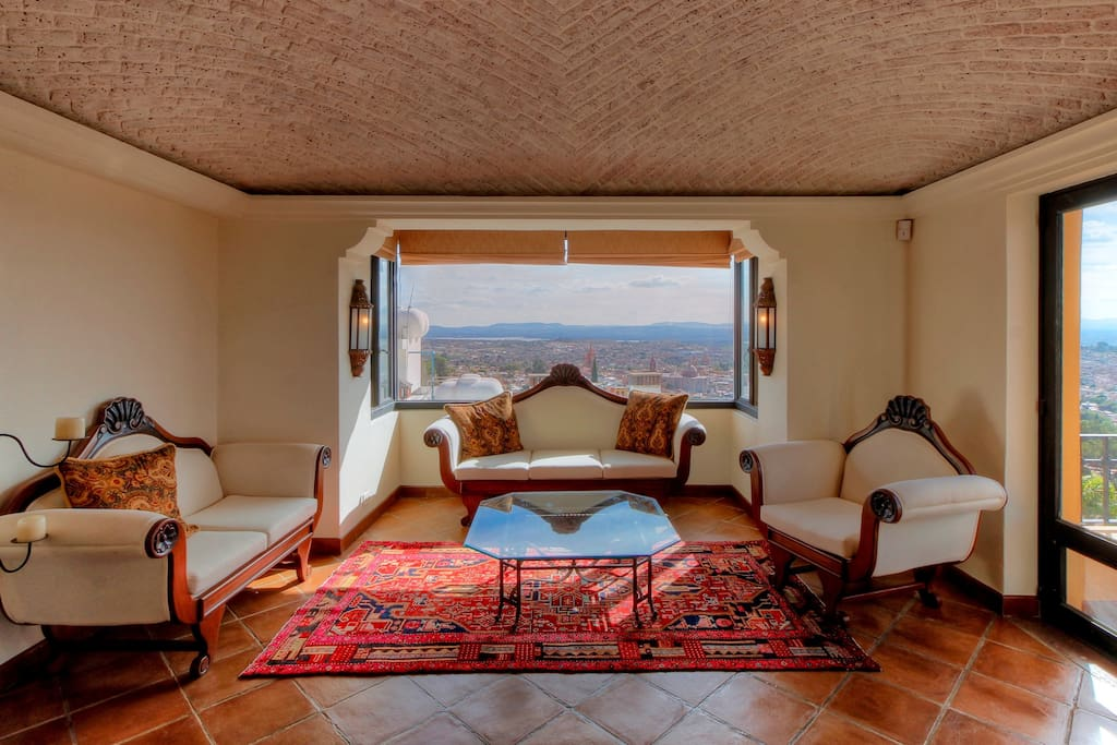 Persian rugs, a bay window and  a stunning view of the Paroquia add to the glamor of this 32 foot room.