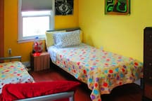 vibrant art by host, vibrant color in this fun room with twin beds.