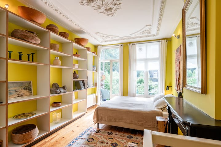 """The """"Yellow Room""""  (55m2) features private bathroom/shower, king-size bed, balcony with garden view."""