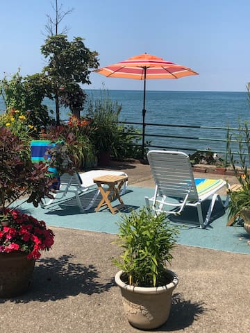 Your private patio is just steps from your guest suite and steps from the beach and lake...mid summer view with flowers in full bloom!