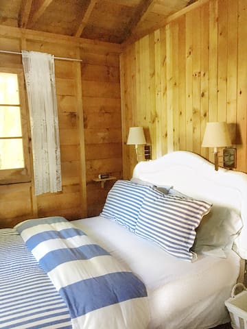 Bedroom #1 in the main cottage. Cozy double bed in corner room with 2 windows overlooking the forest.