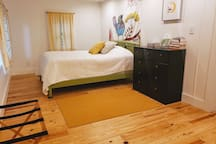 There is a full size bed with painted wood bed frame, FLOR carpet, and plenty of cheery decor.  This bedroom has room for a portable crib also.