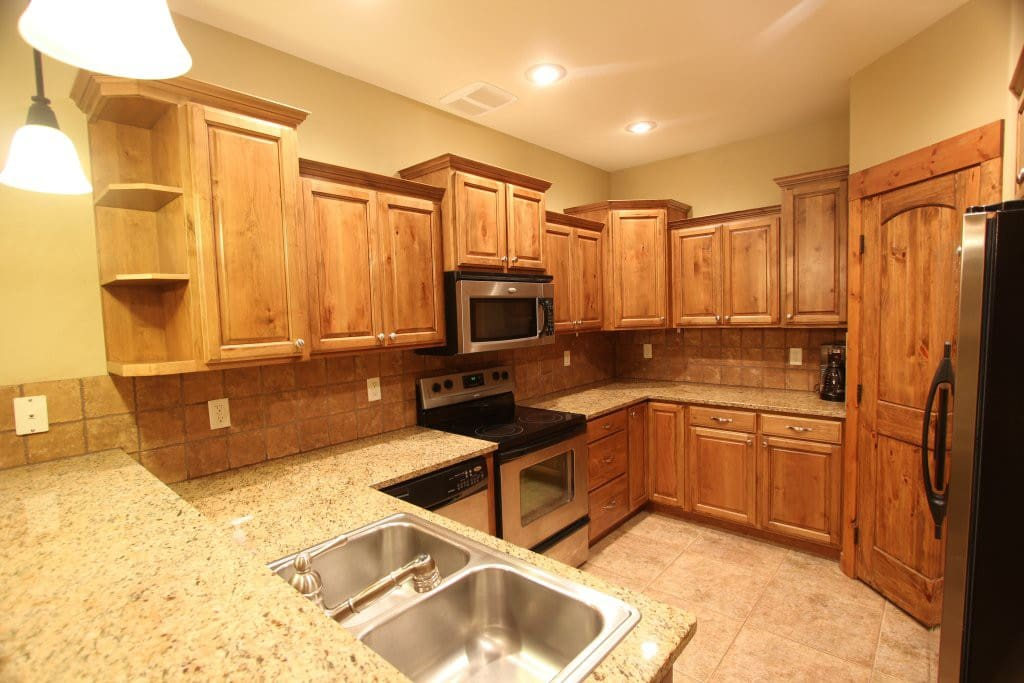 Kitchen with granite counters, stainless appliances, and fully stocked with cooking utensils.