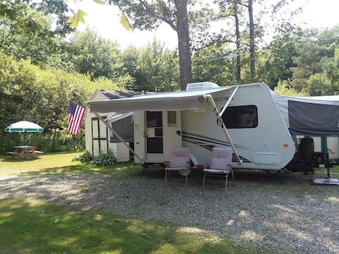 Clean hybrid Camper in country setting.