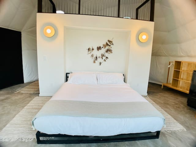 King size bed features organic linens and the locally crafted driftwood art above serves as the anchor of the space