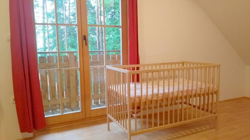 upstairs bedroom with double bed + crib and balcony