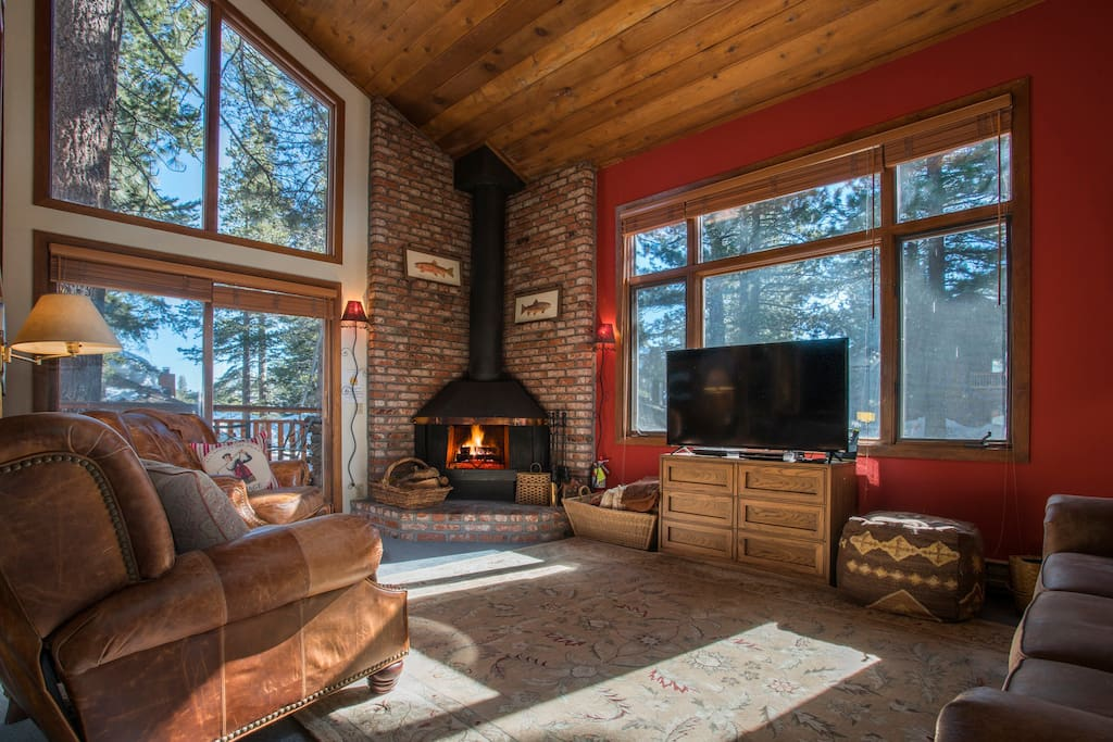 Large living area with high ceilings, grand windows, warm fire, and lovely patio