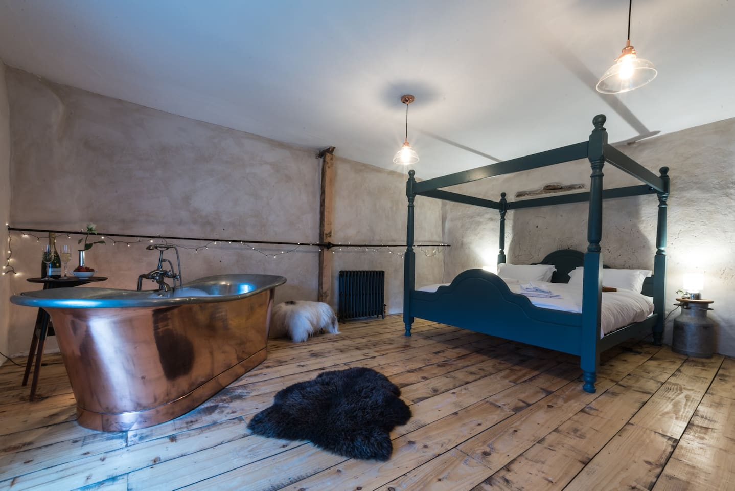 Luxurious bedroom with 4 Poster Super King sized bed and roll-top antique Copper Bath