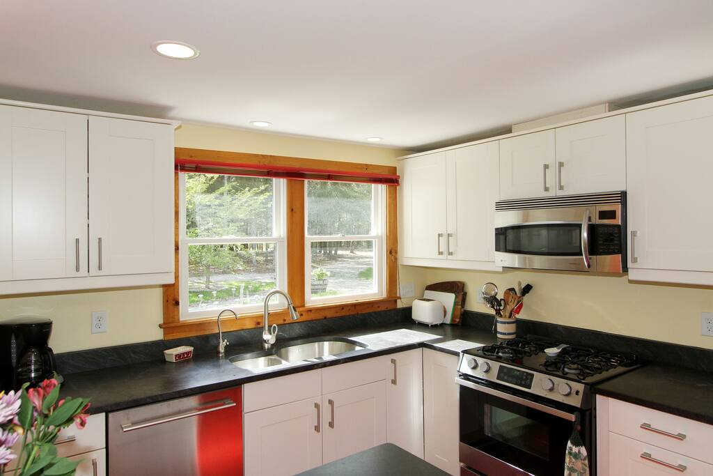 Stainless steel appliances include a gas range and double door refrigerator.