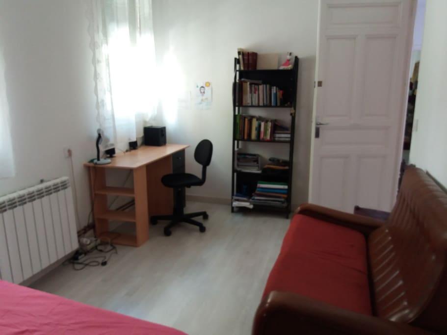 Dormitorio con cama doble y espacio de trabajo