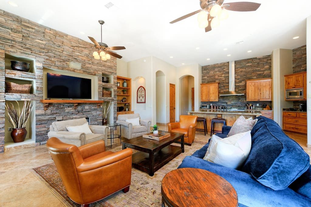 Stone accent walls, fireplace, wet bar, flat screen TV, and plush furnishings in the living room.