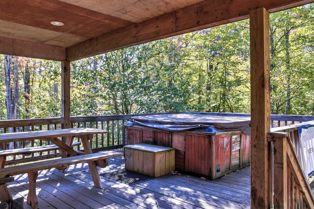 Relax in the private hot tub as the evergreens tower over your cozy spot on the backyard balcony.