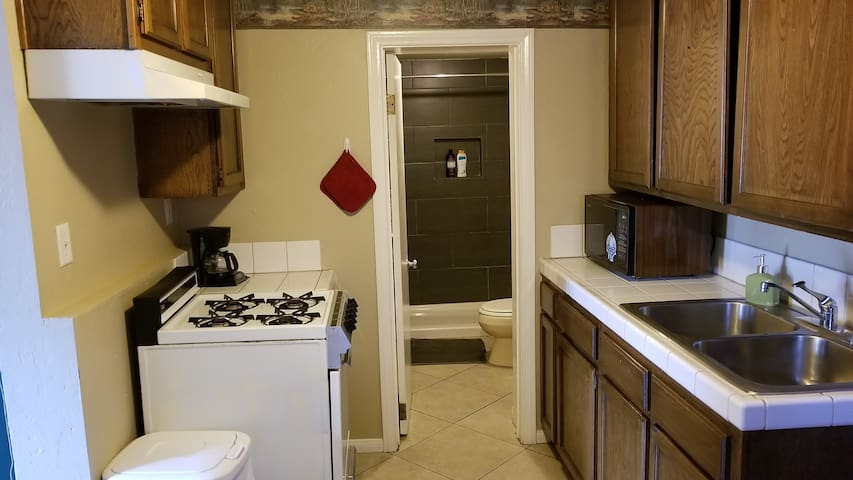 Kitchen with 4 burner stove top oven, microwave and coffee maker.
