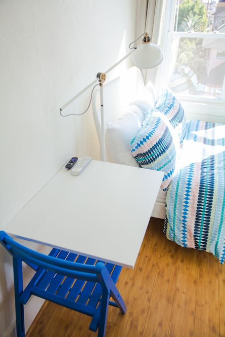 Efficient drop-down table can function as a night stand or eating area.