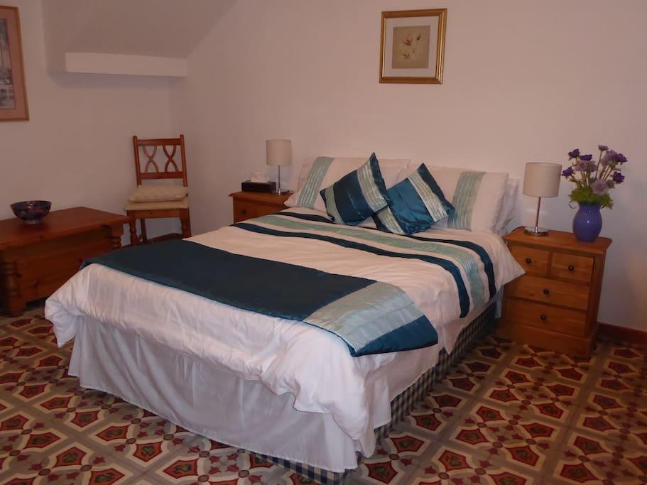 Bedroom 1, double bed. Note tiled floor