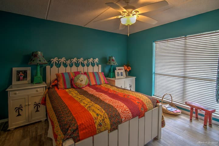"""Bright and cheery is the master bedroom. A wonderful escape to sleep or watch late night tv on the 60"""" smart tv screen on the queen size mattress with a 4"""" foam topper. It's super comfy!"""