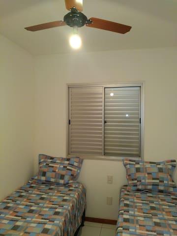 Quarto de solteiro com duas camas box, mesa de estudo com cadeira, ventilador de teto, janela arejada com grades de segurança.
