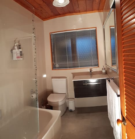 Modern fully tiled guest bathroom with in-built fan wall heater