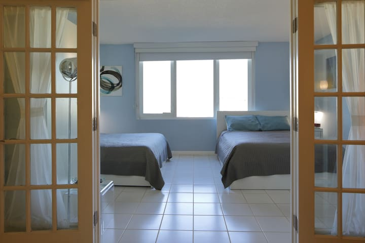 French door entry way into the bedroom, with 2 queen beds and a city/bay view
