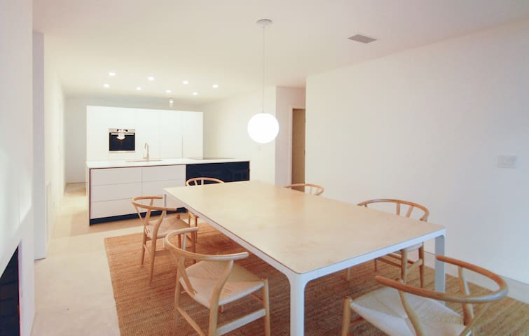 a custom table for eight, two bar stools and a fully equipped kitchen with bosch, smegg and miele appliances, tons of storage, high design quality throughout, a direct-access two-car garage with more storage and free EV charging!