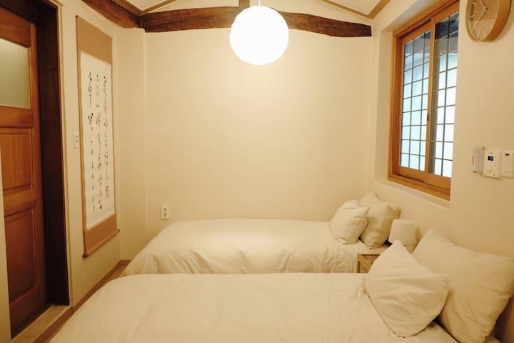 싱글베드 2개 준비된 방입니다. 침대와 침구 패브릭은 모두 무인양품 제품을 사용했습니다. 베개는 두종류로 준비되어있으니 취향에 따라 골라서 사용하세요. 침대 맞은 편 세탁룸에는 간이세면대가 마련되어 있습니다.