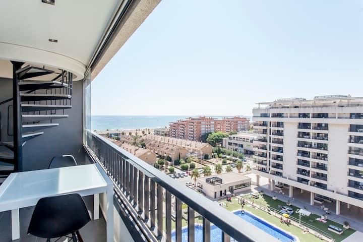 Ático con ampla terraza, vista al mar y piscina.