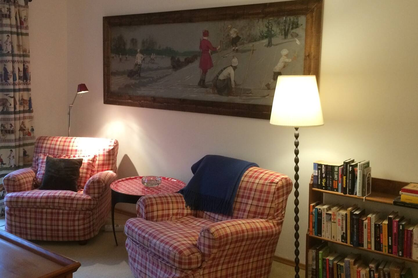Comfortable living room with a large sofa, lounge chairs, balcony towards the village square and a small stove
