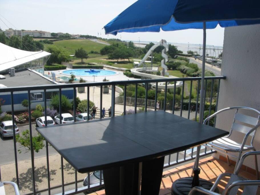 Terrasse équipée d'une table et quatre chaises avec vue sur la mer