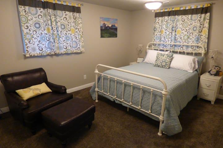 Bedroom #1: queen bed, nightstands, chair/ottoman, closet, mirror, and 2 daylight windows.