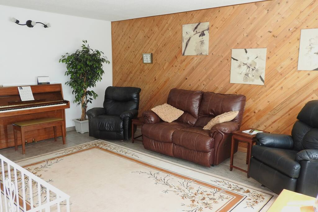 Living room, bright and roomy, piano, comfortable seating for four: two rocker/recliner armchairs and a recliner loveseat.