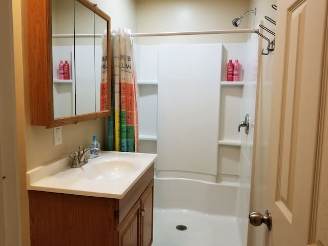 Private bathroom with basic amenities including hand soap, shampoo, towels, washcloths, hand towels.