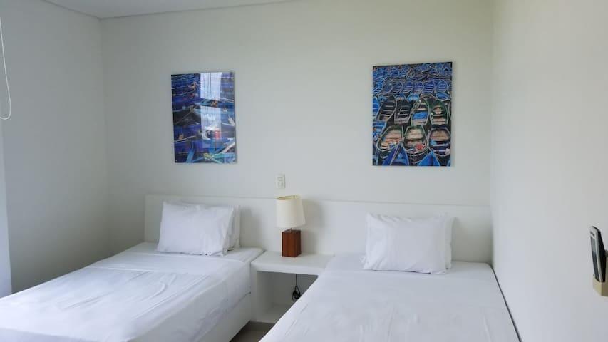 Habitación adicional con dos camas semidobles y un baño externo.
