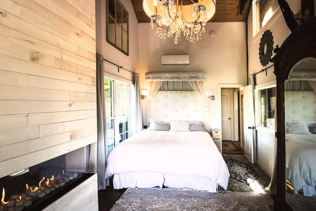 Master bedroom with fireplace and window overlooking horse stalls
