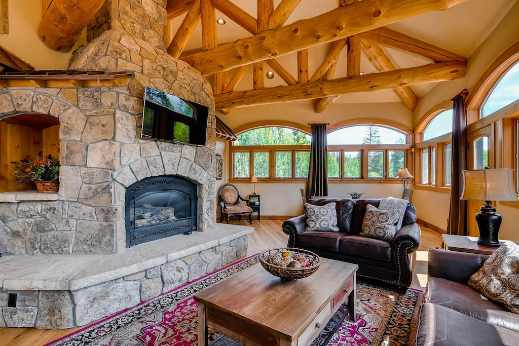 with gas fireplace, TV and door leading out to deck with hot tub