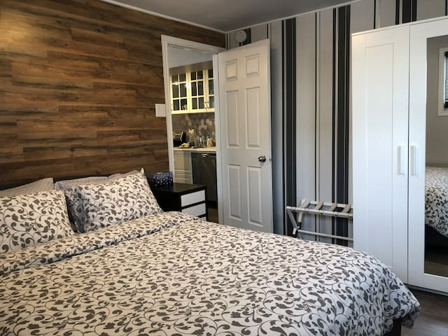 Bedroom with queen size bed and two windows