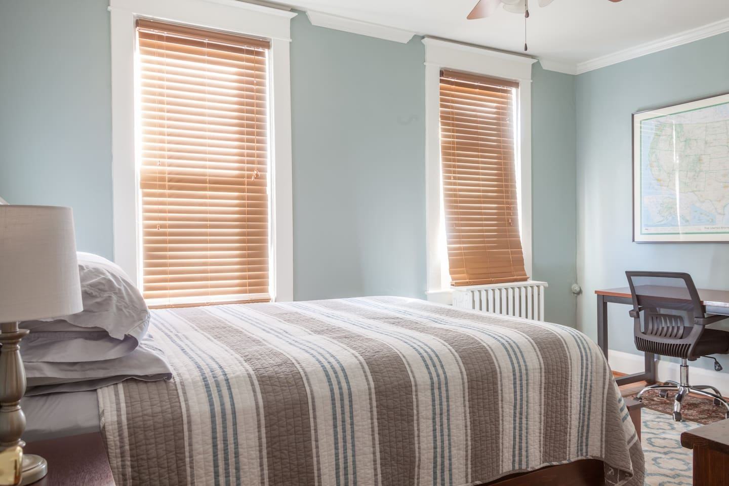 Renovated guest bedroom with comfortable bed, desk, closet, and coffee maker.