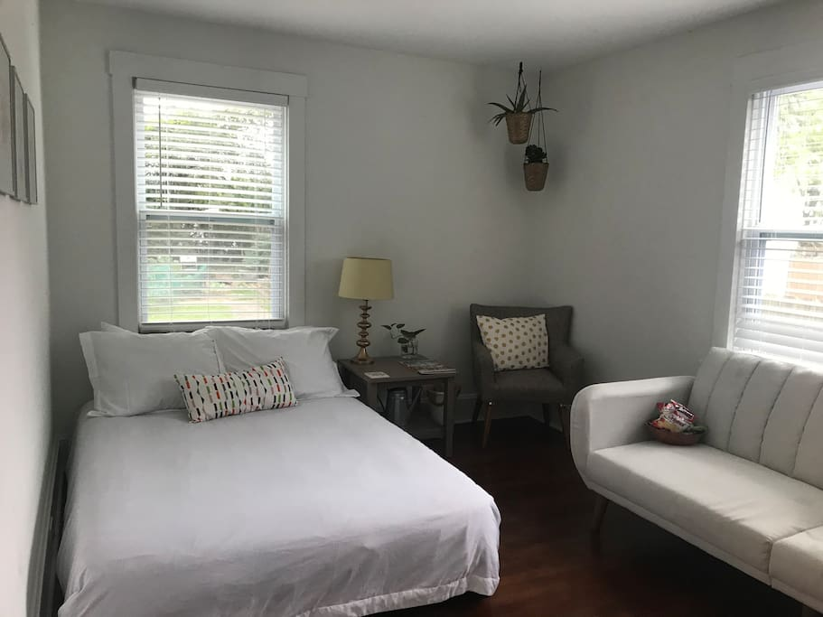Bright and airy private guest room features tons of natural light, a full size bed, and modern convertible sofa.