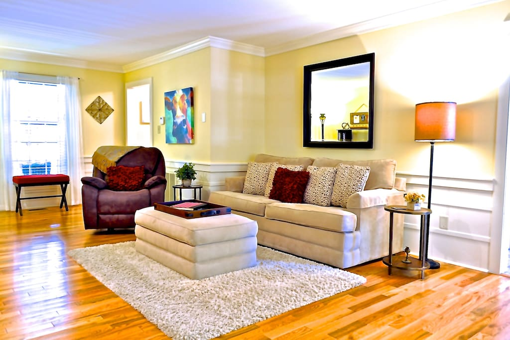 Living room with hardwood floors and comfy seating, faces screened porch