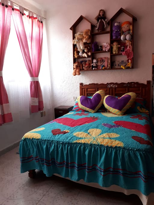 Cama matrimonial con ropa de cama y almohadas para dos personas.