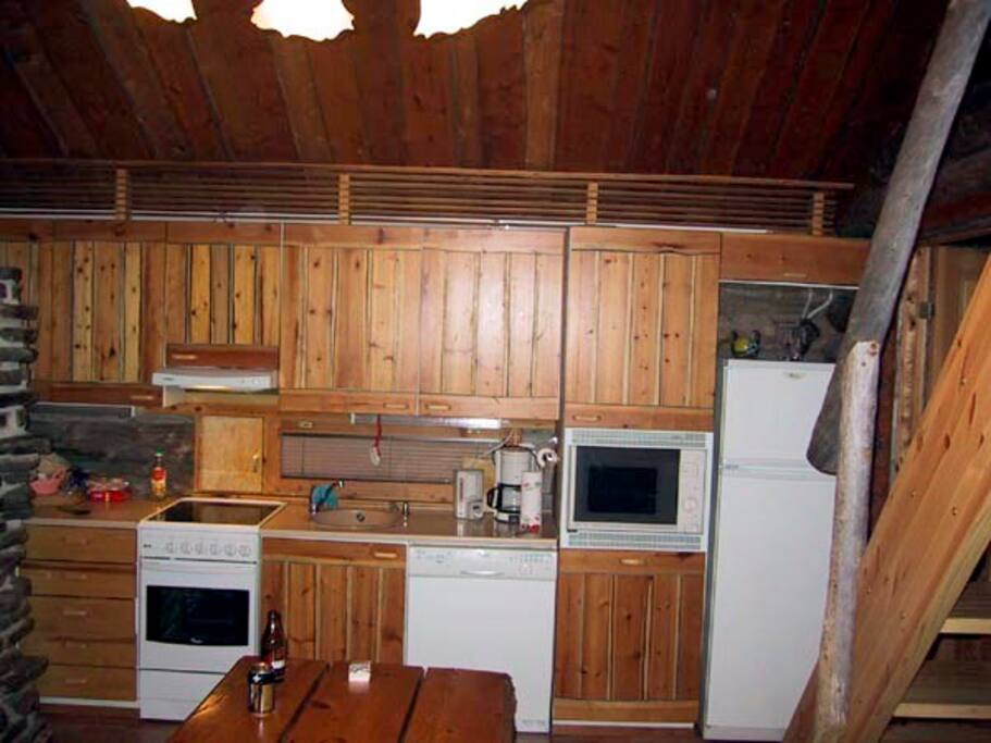 Open kitchen with stove and washing machine, microwave and fridge.