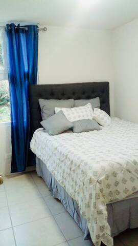 Cama queen size para dormitorio secundario, con una vista a la naturaleza, amplio.
