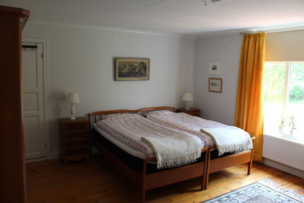 """""""Sommarrummet"""" - går i gult. Utsikt mot berget och har även en liten soffa och bokhylla samt extra walk-in closet."""