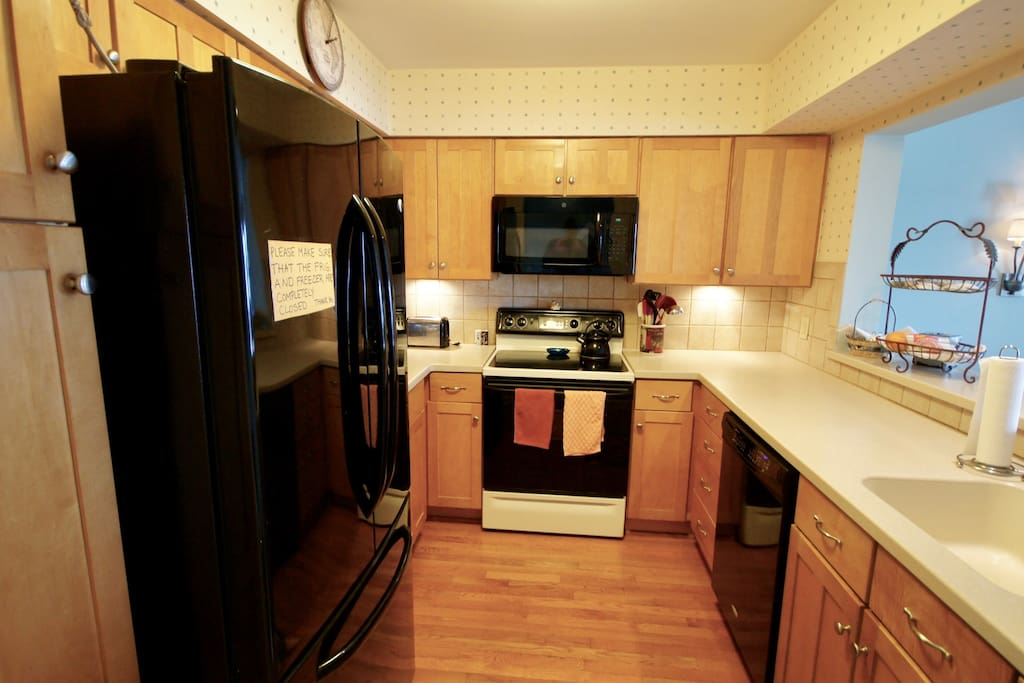 Kitchen with newer appliances and plenty of cabinets and cookware