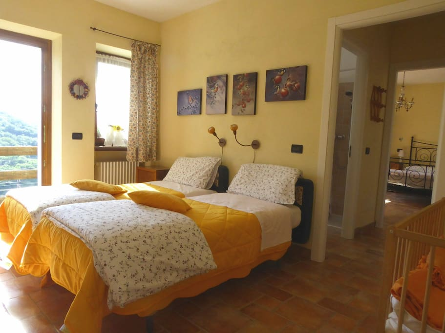 Room with two single beds, connected with the double bed bedroom. / Camera doppia con letti singoli, comunicante con camera matrimoniale.