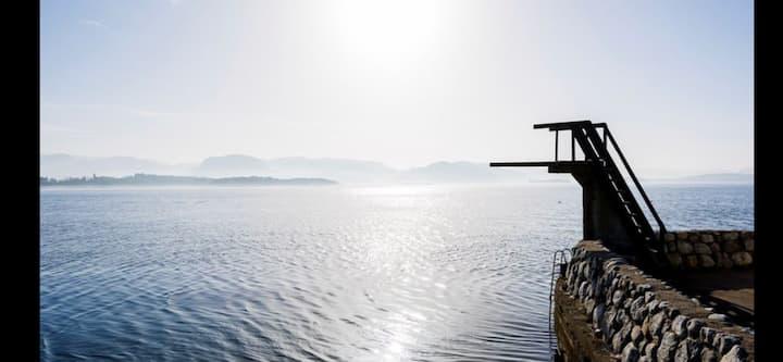 Hus ved sjø med tilhørende båtmulighet.